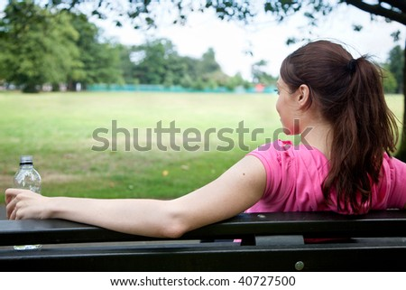 sporty woman resting on a bench after exercising - stock photo