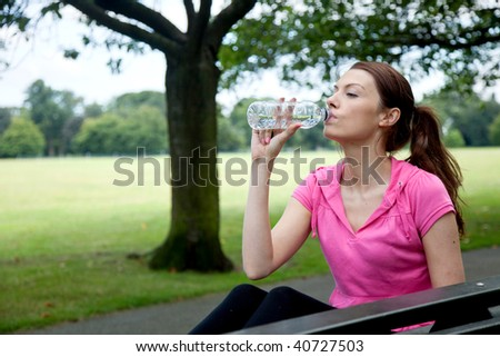 sporty woman resting on a bench drinking water - stock photo