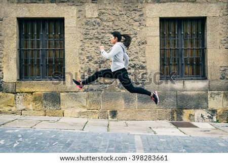 Sporty woman running and jumping in street. Female urban athlete training outdoor. - stock photo