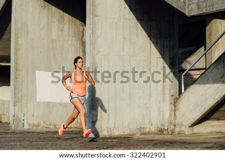 Sporty woman running and training outdoor. Female athlete working out over urban abstract background. - stock photo