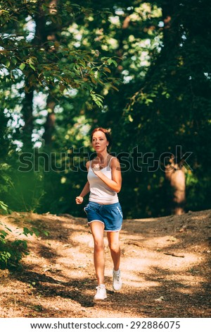 sporty woman running in the summer park - stock photo