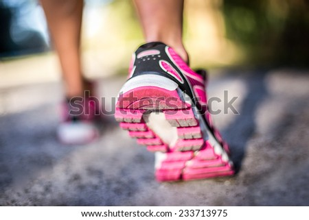Sporty woman running on country road at sunrise. Fitness and workout wellness concept.  - stock photo