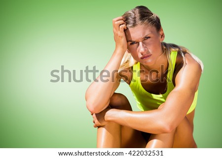 Sporty woman sitting down and feeling disappointed against green vignette