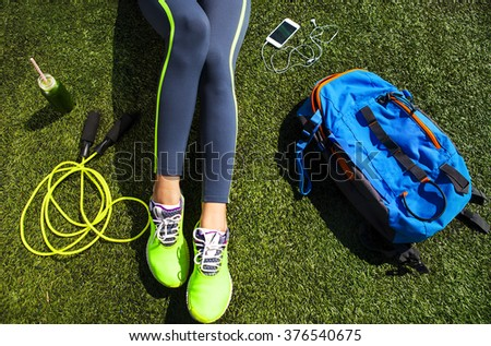 Sporty woman sitting on the green grass with phone with empty screen,  jump rope, backpack and drink bottle