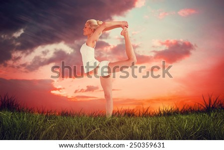Sporty woman stretching body while balancing on one leg against red sky over grass - stock photo