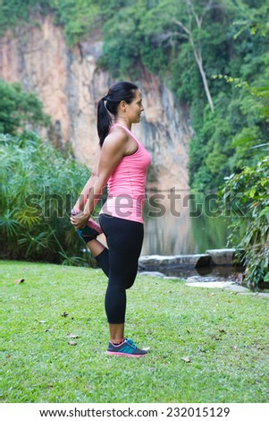 Sporty woman stretching her thigh, exercising in the park - stock photo