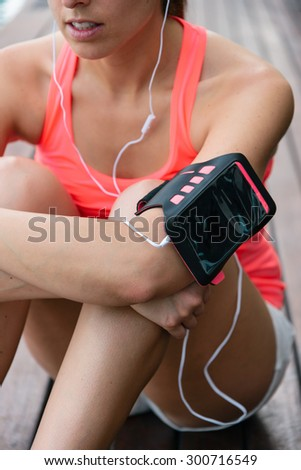 Sporty woman taking a fitness workout rest for listening music through earphones. Female athlete wearing cellphone armband.