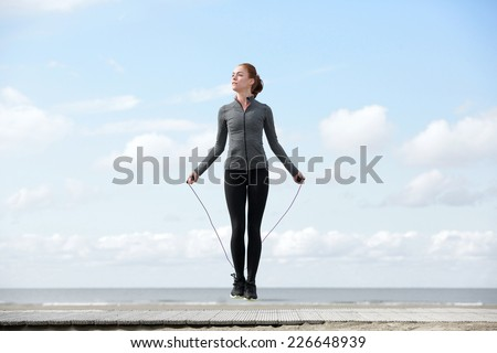 Sporty woman warming up with jump rope outdoors - stock photo