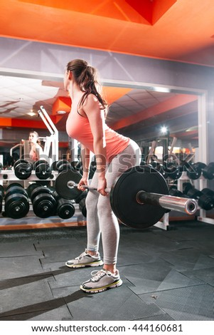 Sporty woman with barbell looking at mirror at herself. Female workout at gym. Fitness girl training with heavy weights against mirror reflection - stock photo