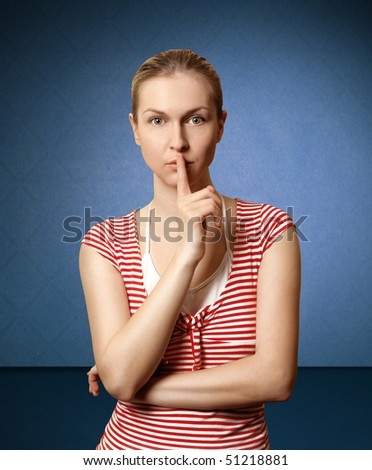 Sporty woman with finger near mouth in blue room - stock photo