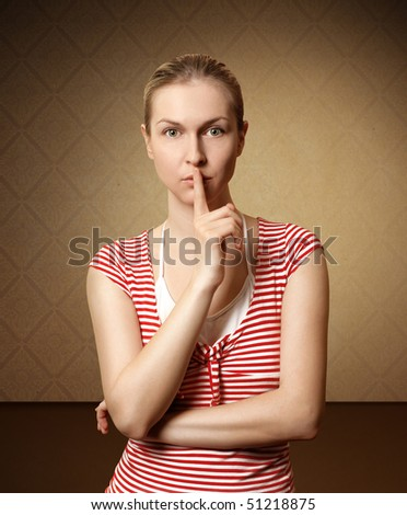 Sporty woman with finger near mouth in brown room - stock photo