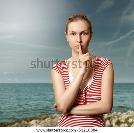 Sporty woman with finger near mouth on the beach - stock photo