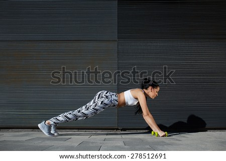 Sporty woman with perfect figure and buttocks shape doing press ups with dumbbells near copy space wall for your text message, fit female in workout gear doing push-ups on black background outdoors - stock photo