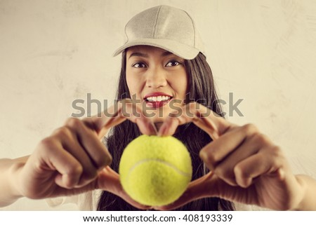 Sporty woman with tennis ball - stock photo