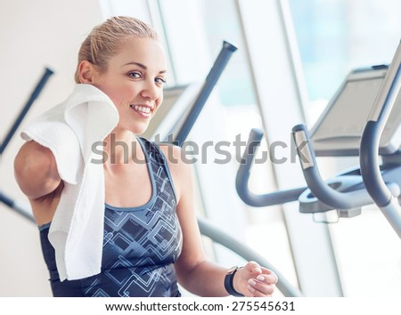 Sporty woman with towel in gym after training - stock photo