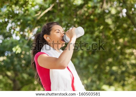 Sporty woman with towel on shoulders drinking water and listening to music - stock photo