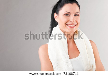 sporty woman with towel on shoulders on grey background