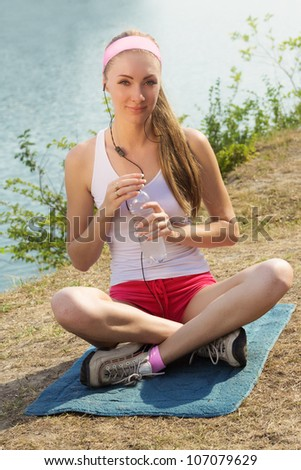 Sporty woman with water and headphones on river bank relaxing