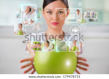 Sporty woman working out using modern virtual interface - stock photo