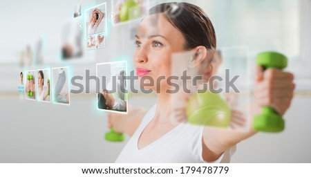 Sporty woman working out using modern virtual interface. Online fitness trainer concept - stock photo