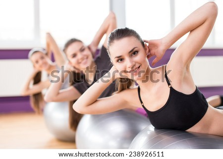 Sporty women are doing sit-ups on the exercise balls. - stock photo