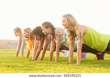 Sporty women doing push ups during fitness class in parkland - stock photo