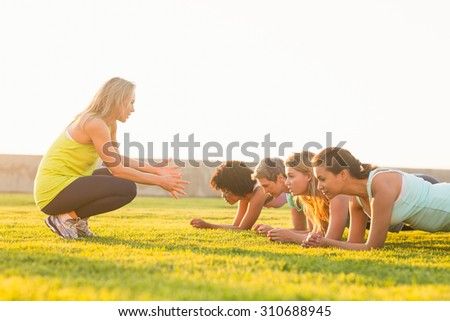 Sporty women planking during fitness class in parkland