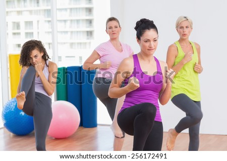 Sporty women practicing kickboxing at fitness studio - stock photo