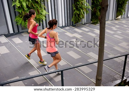 sporty women running down stairs outdoors for morning workout - stock photo