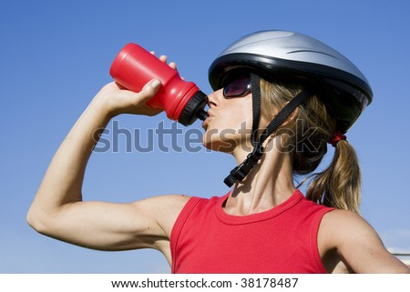 Sporty women with a cycle helmet drinking water - stock photo