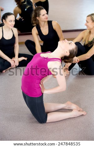 Sporty yoga girl exercises, doing yoga asana Ustrasana or Camel Pose, stands on her knees in class while stretching her back, group of friends watching on the background - stock photo