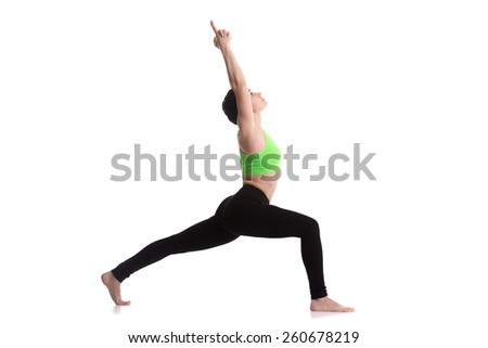 Sporty yoga girl on white background doing exercises for legs muscles, standing in Warrior 1 asana, Virabhadrasana I, back foot on the toe - stock photo