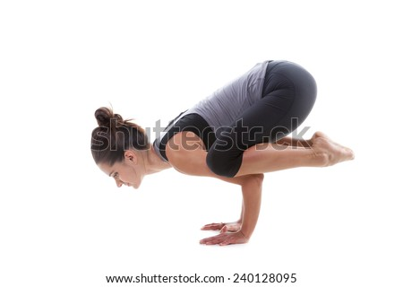 Sporty yoga girl on white background doing handstand or pose bakasana (Crane pose) - stock photo