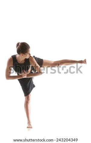 Sporty yoga girl on white background practicing side leg swings - stock photo