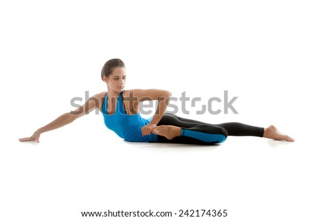 Sporty yoga girl on white background stretching her leg muscles - stock photo