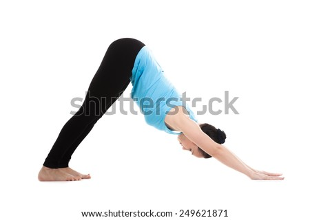Sporty yogi girl doing yoga exercises stretching in pose adho mukha shvanasana (downward-facing dog, downward dog, down dog), isolated on white background - stock photo
