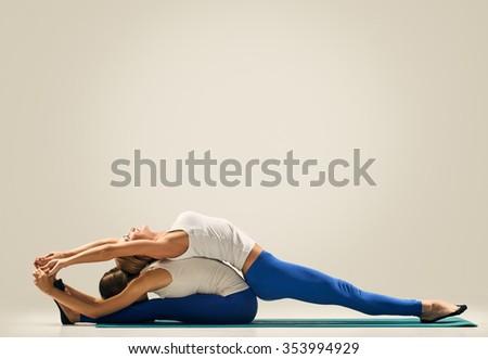 sporty yogi sisters doing fitness training. studio shot. pair, couple yoga - stock photo