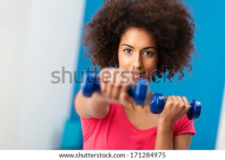 Sporty young African American woman working out with dumbbells in the gym extending her arm towards the camera with a determined expression - stock photo