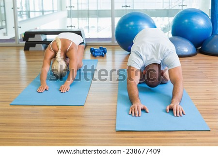 Sporty young couple in bending posture at the fitness studio - stock photo