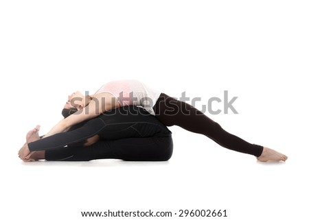 Sporty young couple on white background doing acroyoga, fitness or pilates practice in pair, yoga with partner, paschimotanasana and backbend, studio shot, full length - stock photo