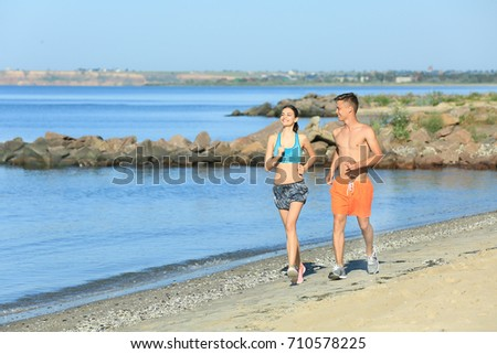 Sporty young couple running on sea beach at resort