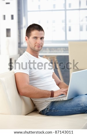 Sporty young man browsing internet at home, sitting on sofa.?