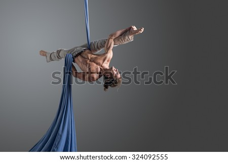 Sporty young man doing exercise with elastics, aerial silk ribbons, aerial. Sport training gym and lifestyle concept. Anti-gravity yoga.