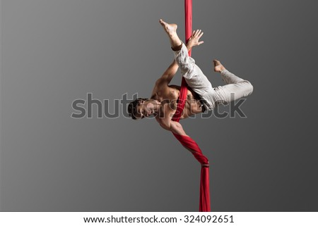 Sporty young man doing exercise with elastics, aerial silk ribbons, aerial. Sport training gym and lifestyle concept. Anti-gravity yoga. - stock photo