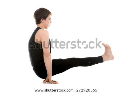 Sporty young man doing yoga or pilates arm balancing exercises, Utpluti Dandasana (Floating Stick asana), Celibates posture, Brahmachariasana, L sit pose, for abdominal muscles, thigh, arms - stock photo