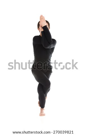 Sporty young man on white background in yoga Eagle Pose, Garudasana, exercise for ankles, calves, thighs, hips and shoulders