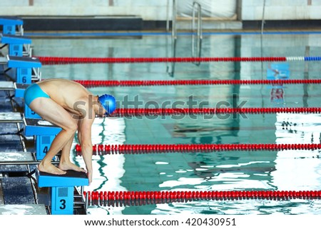 Sporty young man preparing to jump into the water in the swimming pool - stock photo