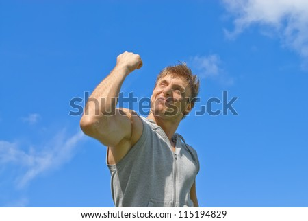 Sporty young man showing his strength. Outdoor training. - stock photo