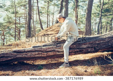 Sporty young man sitting on fallen tree trunk and tying shoelaces outdoor in the pine forest