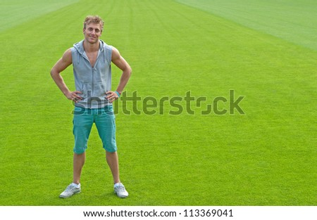 Sporty young man standing on green training field, smiling.